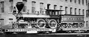 "#87, delivered - from the  of .  This is a 5 ft (1524 mm) gauge 4-4-0 with 54 in (1.37 m) drivers.  Shown during delivery on flatcars due to gauge incompatibility.  Note the elaborate ornamentation.  #87 is a wood-burner with a spark-arresting ""balloon"" stack."